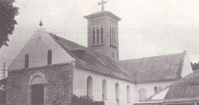 Façade, transept et clocher en pierre : œuvre du Père Offrédo