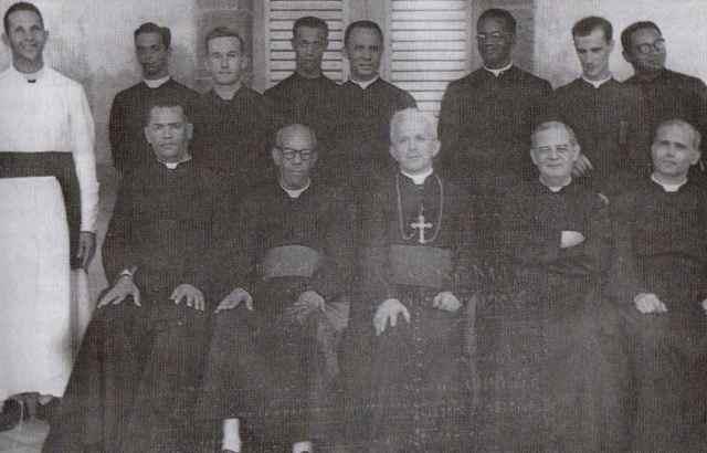 Georges Magloire et Mgr Gay entouré du clergé local
